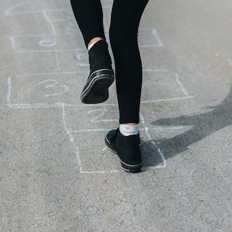 Girl jumping in chalk boxes drawn on asphalt