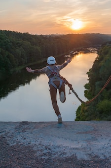 Girl jumping from the bridge. a woman with an incredible time is engaged in freestyle in bungee jumping. a young woman performs a reverse trick in bungee jumping. jump at sunset extreme young.
