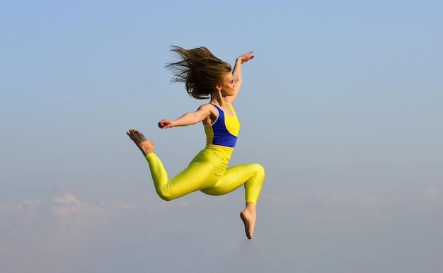 高くジャンプする女の子。動きのあるスポーツ。エネルギーに満ちています。魅力的な若いスポーティな女性が屋外ジムで運動しています。朝の運動。ウクライナの国民体操選手。アクロバットと体操。