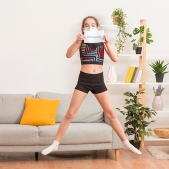 Girl jumping and holding stay home message