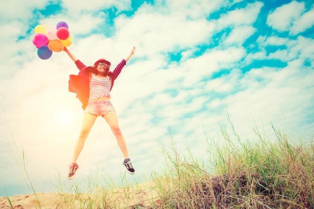 Девочка прыгает на пляже с цветными воздушными шарами