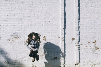 Girl jumping near white wall