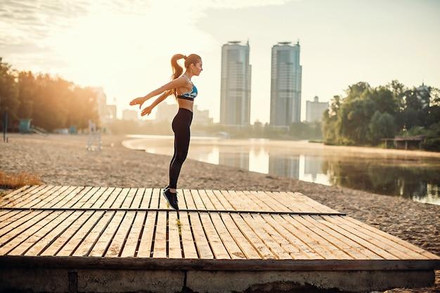 川の海岸に木製のプラットフォームでジャンプの女の子