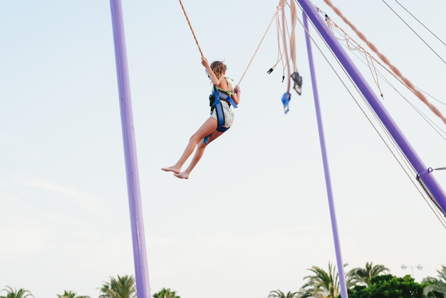Girl jumping on a trampoline helped by ropes at a fair.