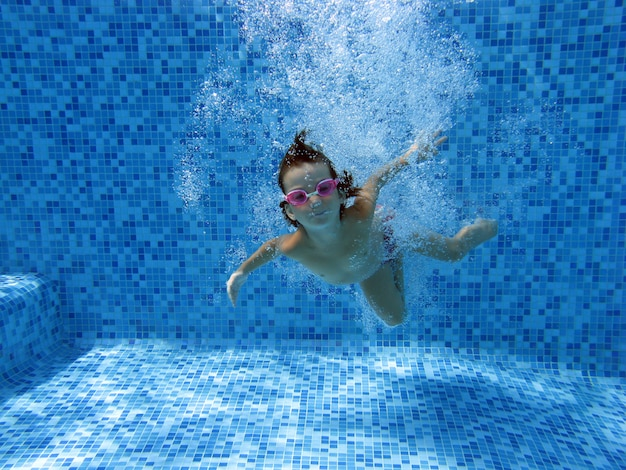 Girl jumps and swims in pool underwater