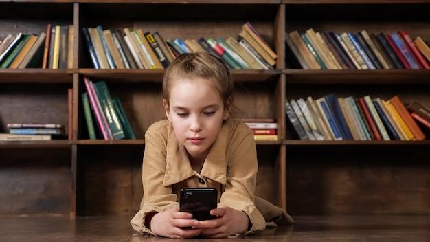 갈색 재킷을 입은 여학생은 도서관에 색색의 책이 있는 나무 책장에 앉아 검은색 스마트폰으로 온라인 게임을 한다