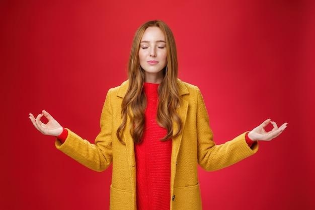 소녀는 명상으로 스트레스를 풀고 노란색 코트를 입고 눈을 감고 무드라 제스처로 손을 옆으로 뻗고 연꽃 자세로 빨간색 배경에 요가를 하는 것으로 안심하는 모습을 유지합니다.