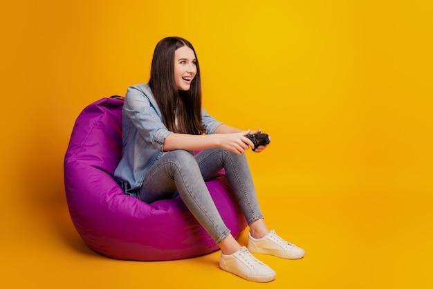 소녀는 비디오 게임을 하는 동안 조이스틱을 손에 들고 빈백에 앉아