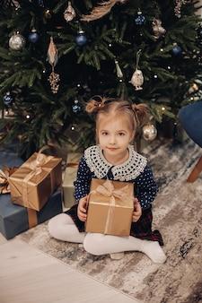 그녀의 다리를 자신 아래에 유지하고 선물 상자를 복용하는 소녀