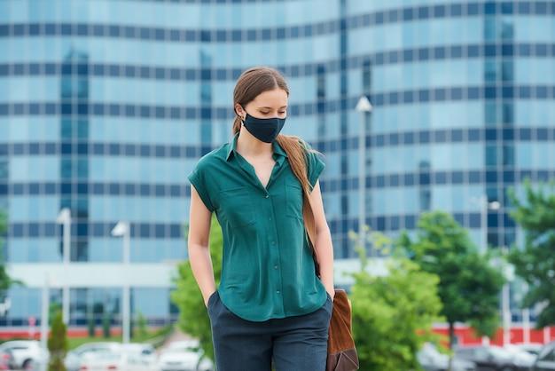 사회적 거리를 유지하는 소녀는 코로나 바이러스의 확산을 피하기 위해 보호 마스크를 착용합니다.