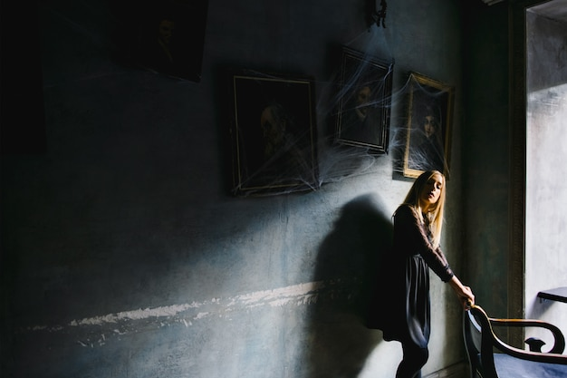 A girl keeps for a chair and leans to a wall with paintings in a cafe