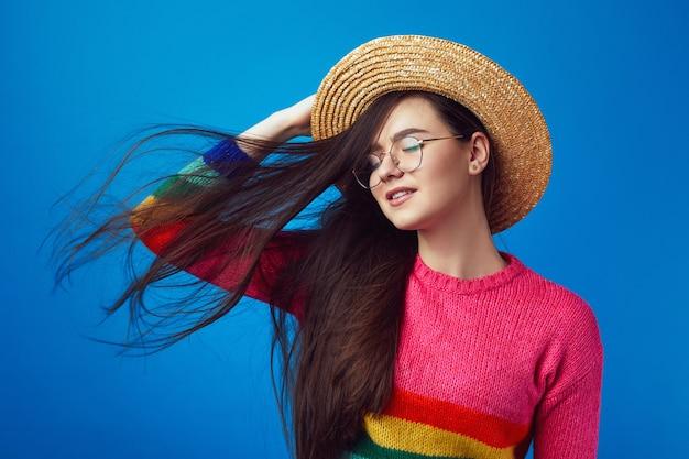 Девушка держит руку на шляпе, закрывает глаза от удовольствия, пока ветер развевает волосы