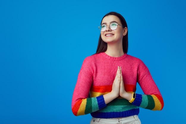 Девушка держит руки вместе, улыбается и смотрит в сторону, носит радужный свитер