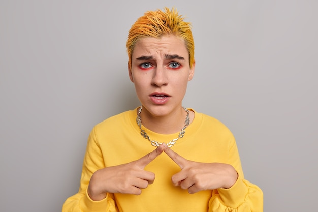 Girl keeps index fingers together tries to make decision thinks about something has vivid makeup dyed hair wears yellow jumper on grey