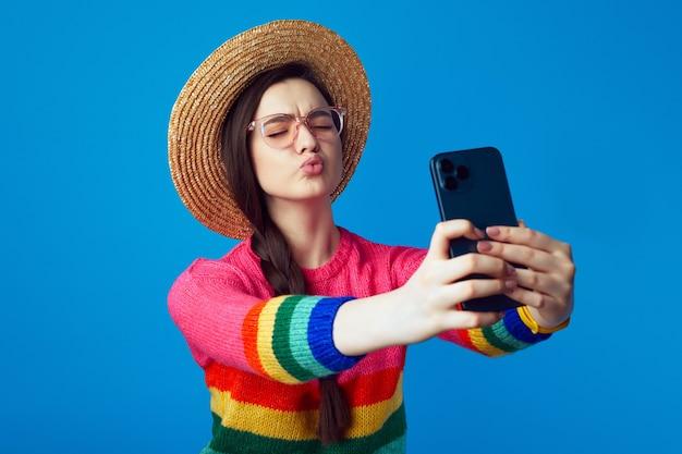 Девушка держит губы сложенными, дует поцелуй в камеру смартфона, делает селфи