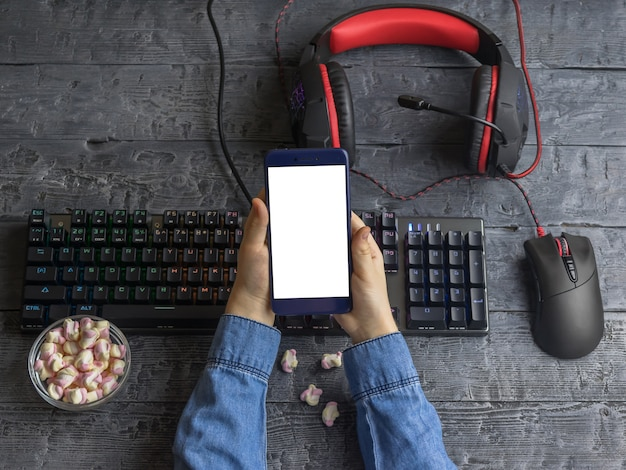 The girl keeps the phone on the background of a desktop with a gaming keyboard, headset and mouse