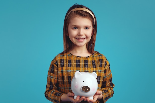 Girl kid holding money box looking excited isolated over blue background
