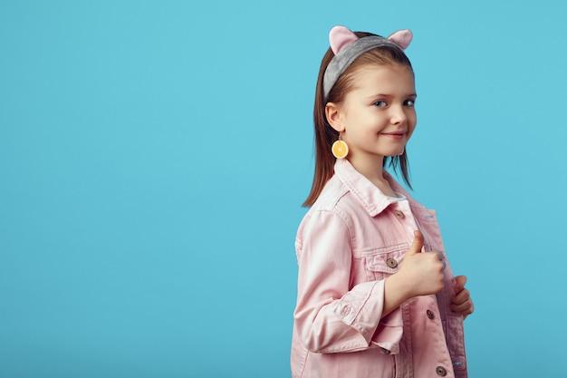 Девушка в розовой куртке очаровательно позирует и показывает большой палец на синем