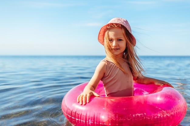 ピンクの円と海で泳ぐピンクのパナマの女の子の子供