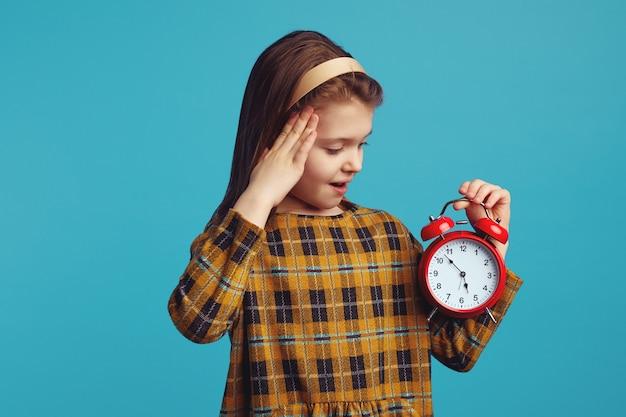 Ребенок девочка смотрит в шоке на будильник, изолированные на синем фоне