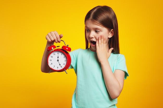 Ребенок девочка смотрит в шоке на будильник на изолированном желтом фоне