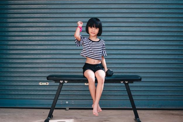 良い健康のためのジム運動でダンベルで運動をしている女の子の子供 Premium写真