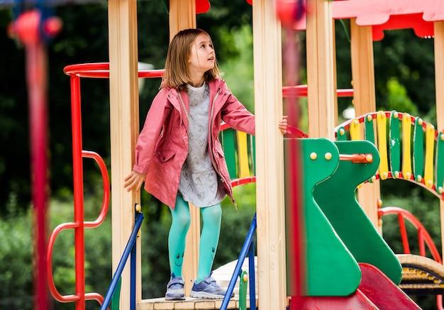 カラフルな公園の遊び場で遊ぶ女の子子供