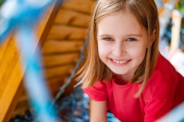 公園のネットで遊び場で遊ぶ女の子の子供