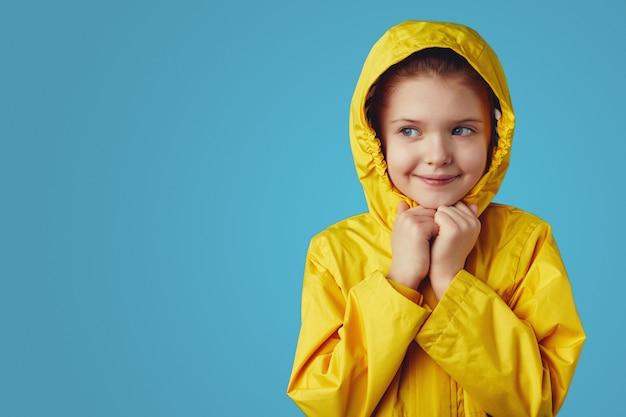 Девочка в желтом непромокаемом плаще держит руки вместе под подбородком