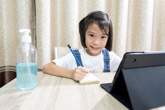 夏休みにタブレットでオンライン学習の女の子の子供