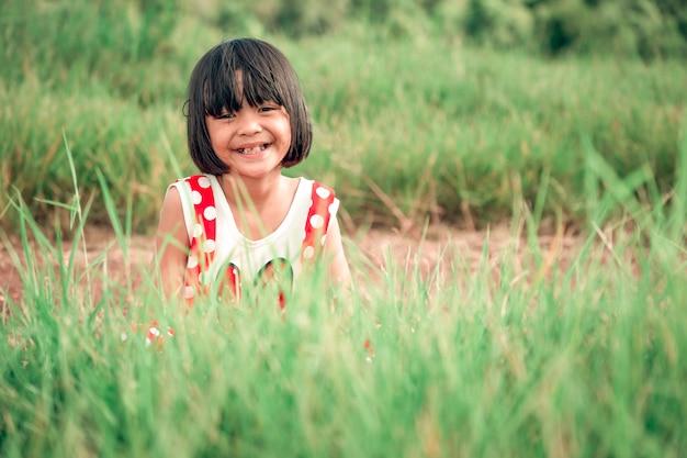 遊んでいる女の子の子供と草原の牧草地の自然に笑顔