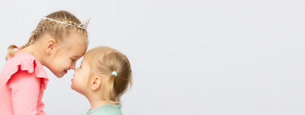The girl kisses her sister on a white background with copy space banner