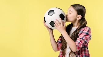 Girl kissing football in studio