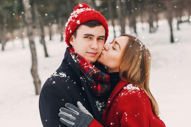 Девушка целует своего парня в снежном парке