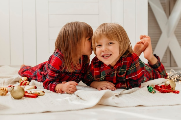 Девушка целует своего брата в щеку