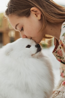 Girl kissing her cute white puppy