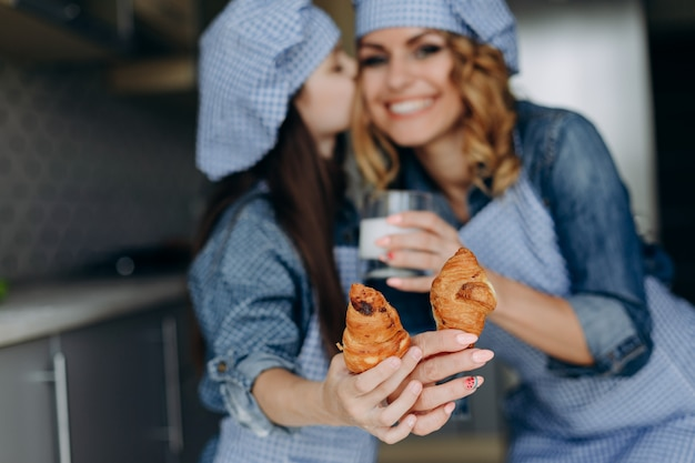 Girl kissing her mother. they holding a croissants and showing it on straight hands