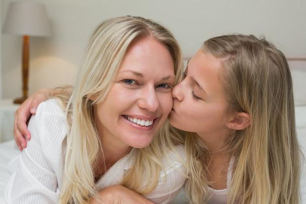 ベッドで頬に母親がキスをする女の子