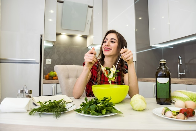 Girl in the kitchen eating a salad of vegetables for a healthy lifestyle