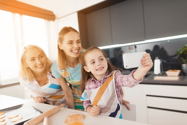 Girl in kitchen makes selfie with her mother and grandmother
