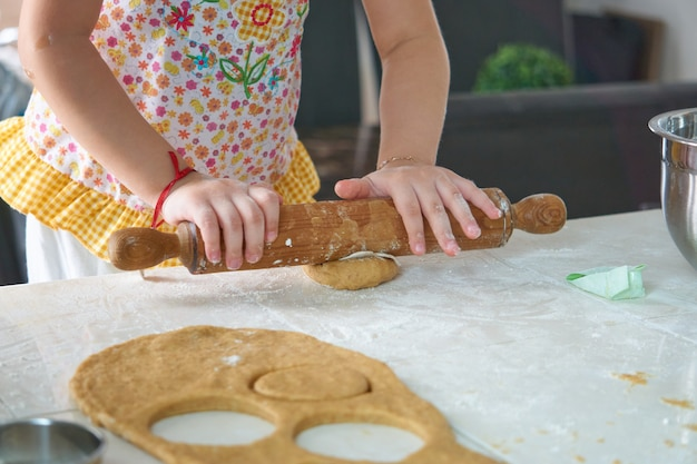 Girl kneadin dough with a roller pin portrait