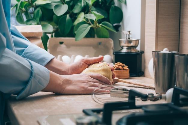 부엌에서 반죽을 반죽하는 소녀 클로즈업. 집에 있는 한 여성이 맛있는 패스트리나 쿠키를 만들기 위해 반죽을 준비합니다. 요리 배경.