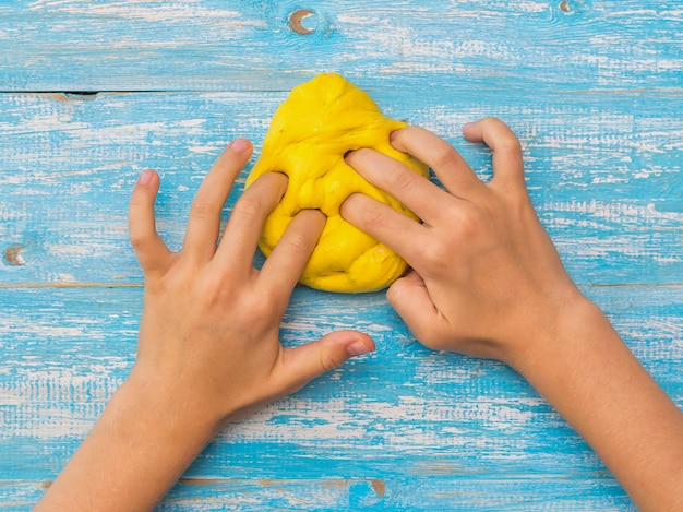 Girl kneads yellow slime on a blue wooden table. toy antistress. toy for the development of hand motor skills.