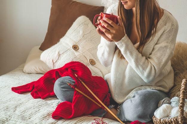 Девушка вяжет теплый свитер с чашкой горячего чая на кровати