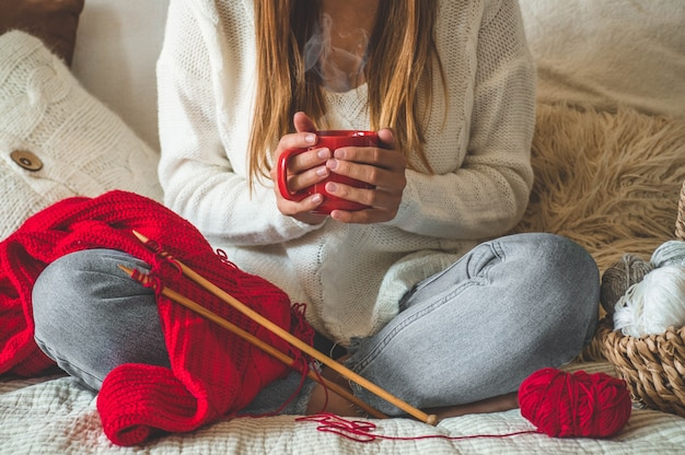 Girl knits a warm sweater with a hot cup of tea on the bed