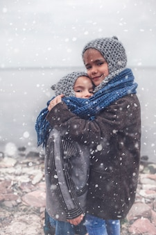 Girl in knitted grey hat hugging her frozen smaller brother