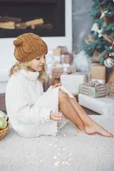Girl in knitted hat near christmas tree makes a wish for new year.