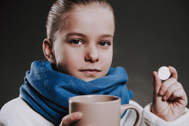 Girl in knitted scarf holds mug with hot beverage and pils.