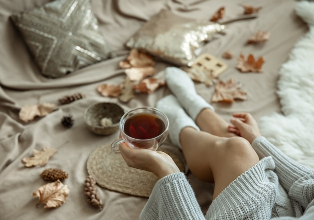 Girl in a knitted sweater holds a cup of tea in her hand, blurred autumn background, home composition.