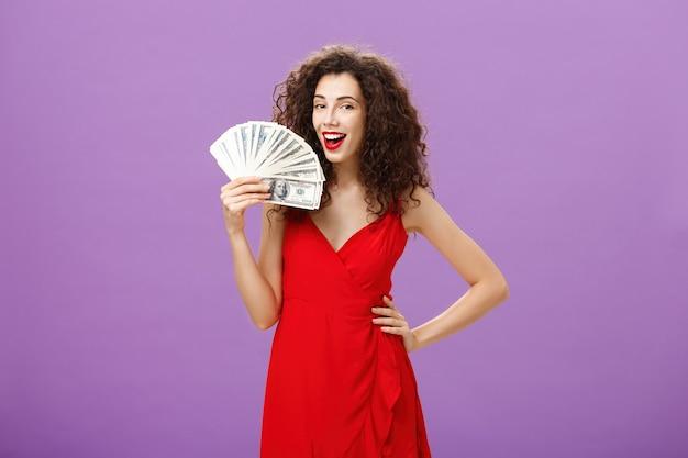 소녀는 돈을 버는 방법을 알고 있습니다. 곱슬머리를 한 우아한 빨간 드레스를 입은 성공적이고 만족스러운 여성은 팔에 많은 현금을 들고 기뻐하는 손 부채처럼 얼굴에 현금을 들고 기뻐하며 웃고 있습니다.